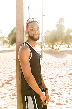 Portrait of smiling black man leaning on beach volleyball net