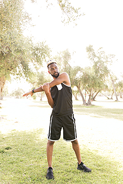 Black man standing in park stretching arm