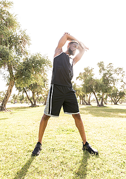 Black man stretching arms in park