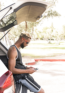 Black man leaning on car hatchback texting on cell phone