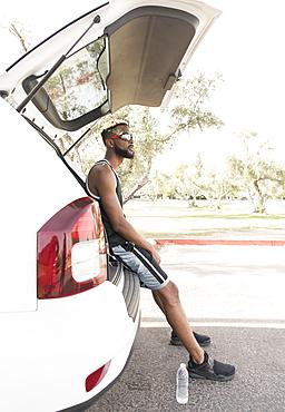 Black man sitting on car hatchback