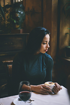 Pensive Caucasian woman drinking coffee