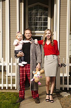 Caucasian couple posing near house with baby daughter