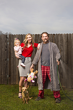 Caucasian couple posing near wooden fence with baby daughter
