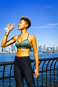 Mixed race woman drinking water at waterfront