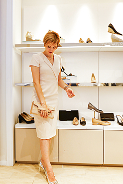 Glamorous Caucasian woman examining purse in store