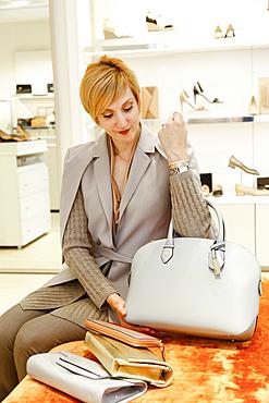 Caucasian woman examining purse in store