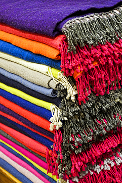 Piles of multicolor blankets with fringe