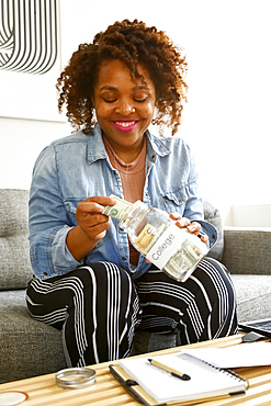 Mixed race woman saving money in jar for college