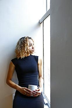 Pensive mixed race woman sitting on windowsill drinking coffee