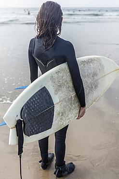 Caucasian woman standing on beach holding surfboard