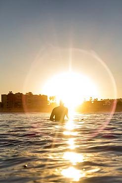 Caucasian man sitting on surfboard in ocean