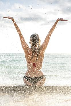 Ocean waves splashing on Caucasian woman wearing bikini
