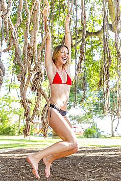 Caucasian woman wearing bikini hanging on branches