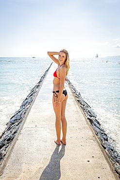 Caucasian woman wearing bikini standing on breakwall