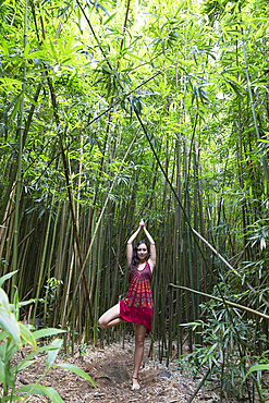 Caucasian woman standing in bamboo forest performing yoga