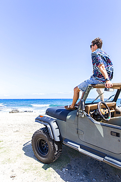 Caucasian man sitting in windshield of convertible car on beach