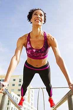 Mixed Race woman balancing on parallel bars