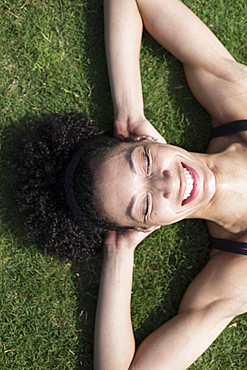 Mixed Race woman laying on grass relaxing,