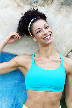 Portrait of smiling Mixed Race woman leaning on wall