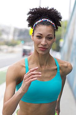 Mixed Race woman running on sidewalk