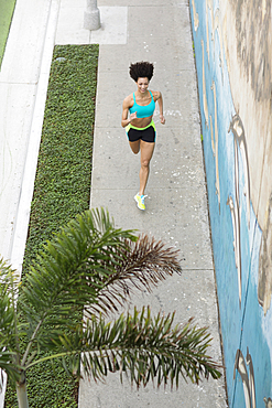 High angle view of Mixed Race woman running on sidewalk near mural