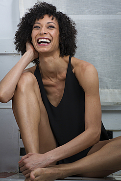 Laughing Mixed Race woman sitting on counter