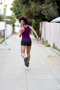 Smiling Mixed Race woman running on sidewalk
