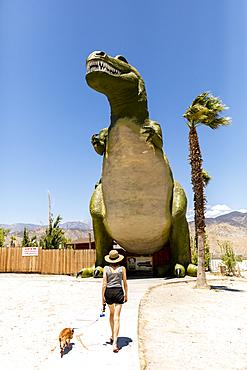 Caucasian woman walking dog near giant dinosaur statue