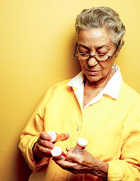 Caucasian woman examining pill bottles