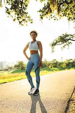 Portrait of serious mixed race woman standing on running path in park