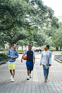 Smiling Black friends walking in park with basketball