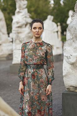 Portrait of confident Caucasian woman standing near statues
