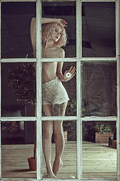 Topless Caucasian woman leaning on window