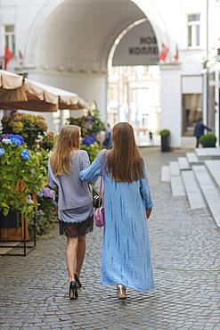 Caucasian women walking arm in arm in cobblestone street