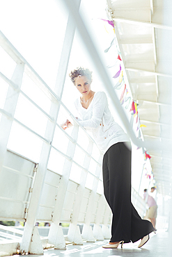 Glamorous Caucasian woman leaning on railing