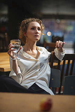 Caucasian woman sitting at table drinking water