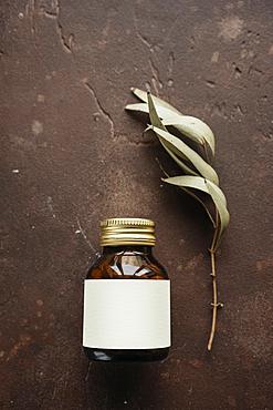 Alternative medicine jar with blank label near leaf