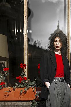 Caucasian woman leaning on flower box near window
