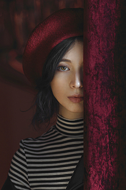 Caucasian woman peeking from behind curtain
