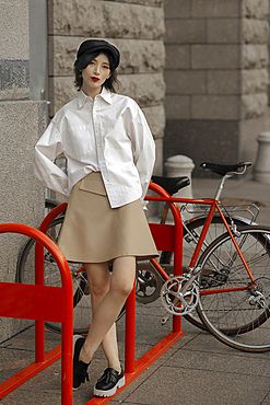 Caucasian woman leaning on bicycle rack