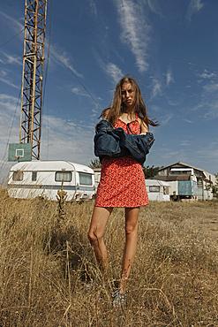 Serious Caucasian woman standing in field near trailers