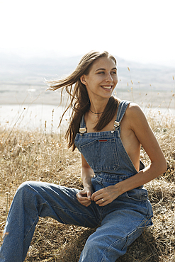Caucasian woman wearing overalls sitting in field