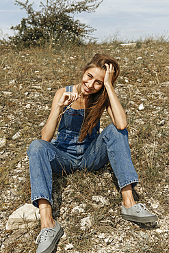 Caucasian woman wearing overalls sitting in rocky field