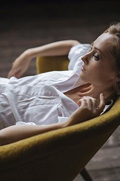 Pensive Caucasian woman sitting in armchair