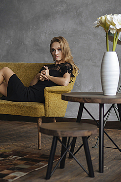 Glamorous Caucasian woman sitting on sofa