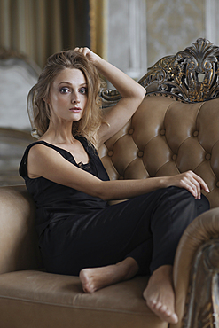 Glamorous Caucasian woman sitting in armchair