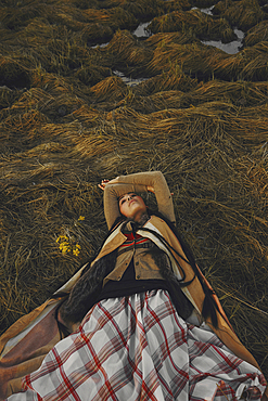 Caucasian woman wearing traditional clothing laying in grass