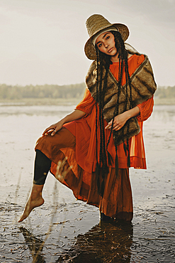 Caucasian woman wearing traditional clothing wading in water