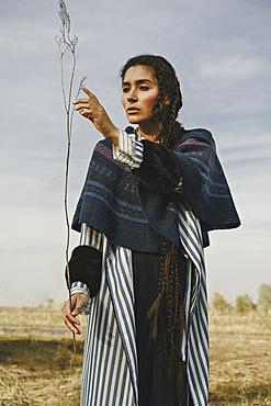Caucasian woman wearing traditional clothing examining twig
